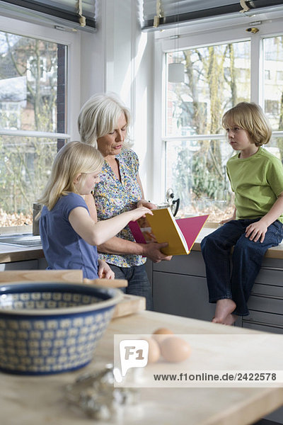 Großmutter und Enkelkinder (8-9) in der Küche