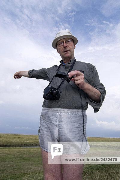 Ein lustig gekleideter Fotograf zeigt nach Kompass wo Norden ist
