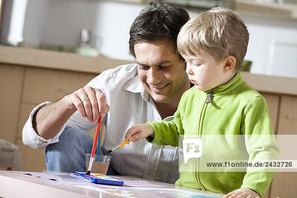 Menschlicher Vater Sohn streichen streicht streichend anstreichen anstreichend