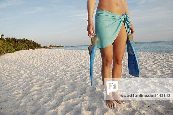 Niedrige Schnittansicht of Frau hält flossen am Strand