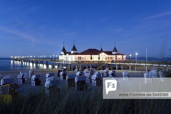 Zusammengerollte Gras und Kapuzen Liegestühle am Strand mit Pier im Hintergrund  Ahlbeck  Usedom  Mecklenburg-Vorpommern Deutschland