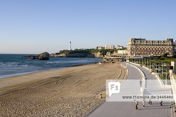 Tourists walking on promenade with hotel and lighthouse in background  Hotel Du Palais  Biarritz  Pyrenees-Atlantiques  Aquitaine  France