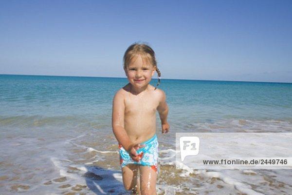 Porträt von kleines Mädchen zu Fuß durch Brandung am Strand