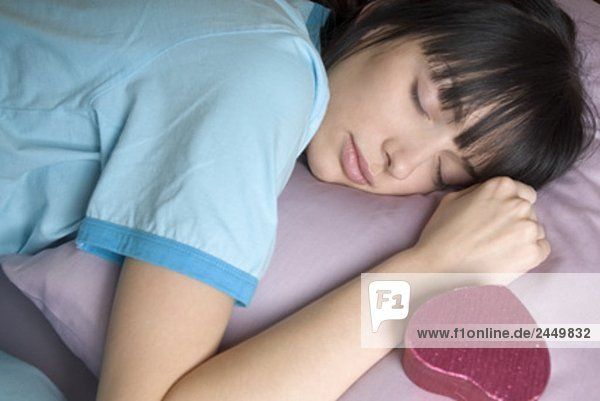 junge Frau schläft mit Geschenk-Box an ihrer Seite
