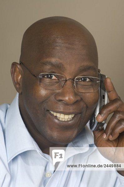 headshot of black businessman talking on mobile phone
