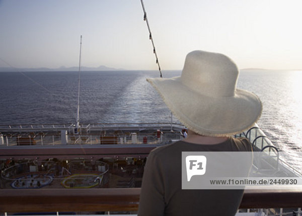 rear view of woman on cruise ship looking at horizon sun is setting