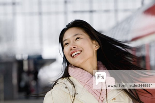 portrait of smiling japanese woman at train station