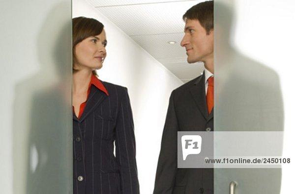 zwei Geschäftsleute stehen Seite an Seite hinter halb offenen Glastür