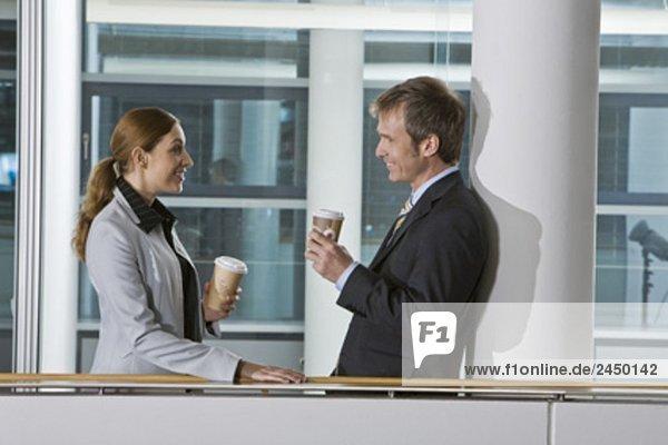 zwei Führungskräfte mit Kaffeepause und Flirten mit einander