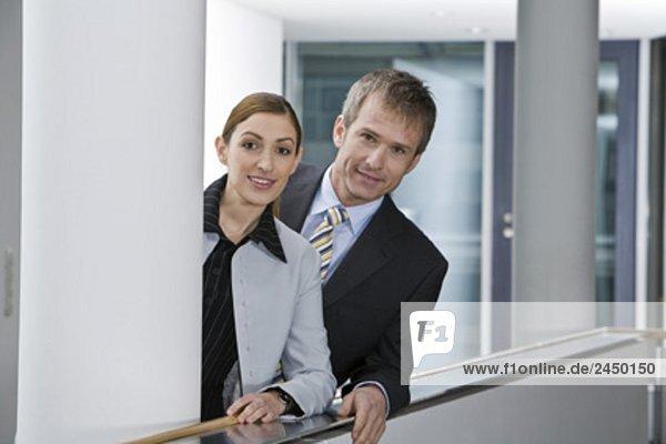zwei Führungskräfte am Geländer in Bürogebäude