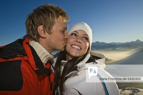 young couple in the mountains man kissing woman on cheek