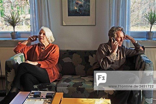 Middleaged paar sitzt auf einer Couch mit ihren Handys