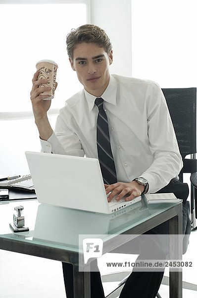 Business man working with laptop is holding a paper coffee cup