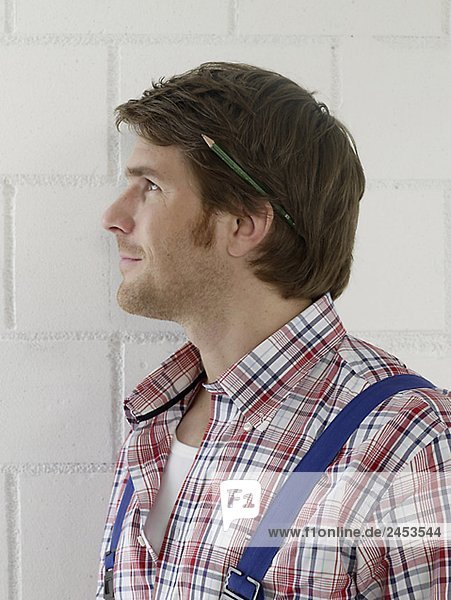 Mann wearing work wear with a pencil behind his ear