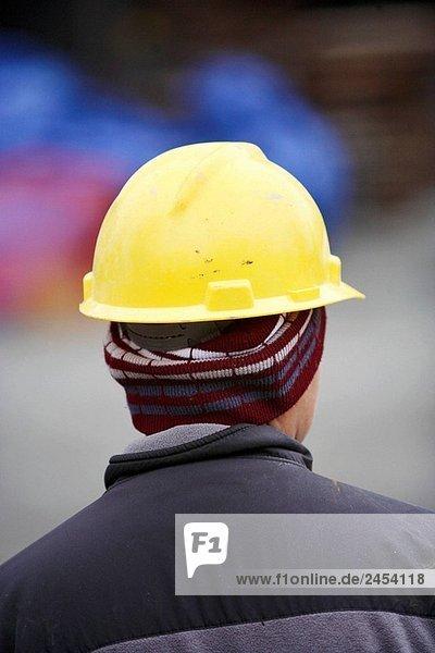 Bauarbeiter mit gelben Schutzhelm hinter