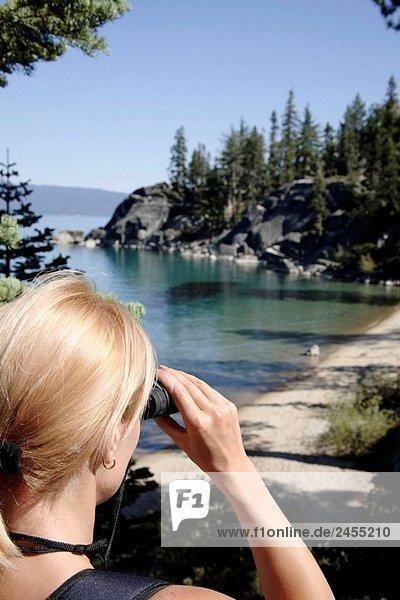 Frau mit einem Fernglas anzeigen einen See
