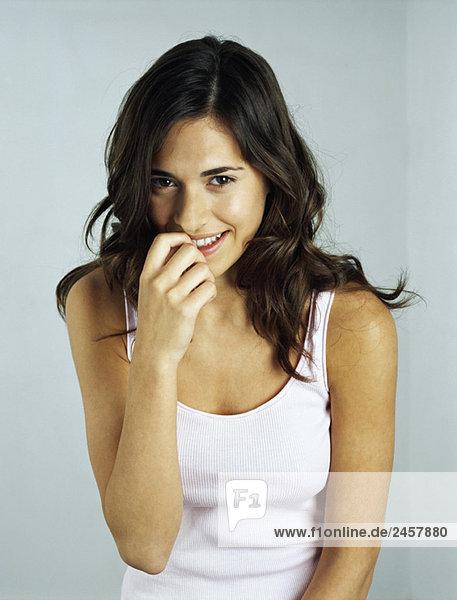 Young woman smiling at camera  biting fingernail  portrait