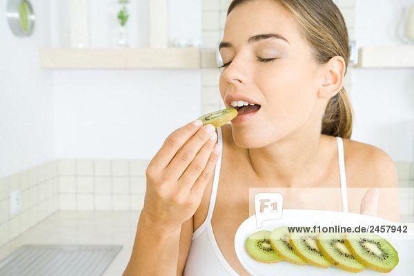 Frau isst frische Kiwischeiben  Augen geschlossen