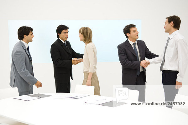 Gruppe von Profis neben dem Tisch stehend  lächelnd  einige Hände schüttelnd