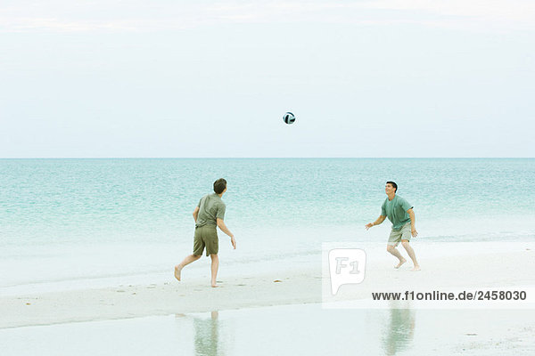 Father and teen son at the beach  both looking up at ball in midair