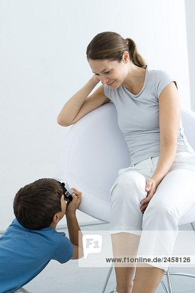 Kleiner Junge fotografiert seine Mutter mit Kamera