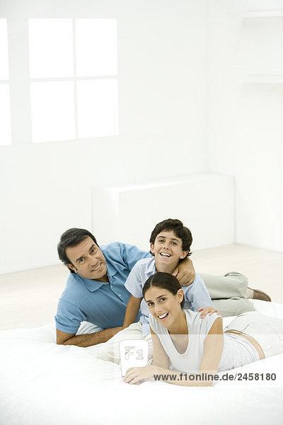Familie zusammen auf Matratze  alle lächelnd vor der Kamera
