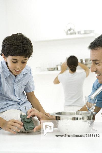 Vater und Sohn in der Küche  Blick auf Spielzeugtank zusammen  Frau im Hintergrund