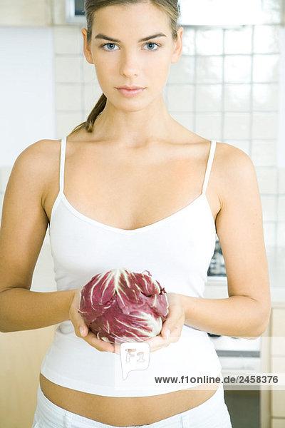 Junge Frau mit einem Kopf aus Radicchio-Salat in der Küche