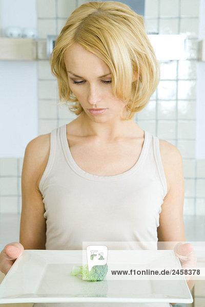 Frau hält Teller mit einem Stück Brokkoli,  nach unten schauend