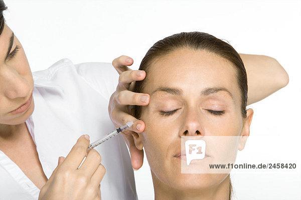 Frau erhält Botox-Injektion  Augen geschlossen
