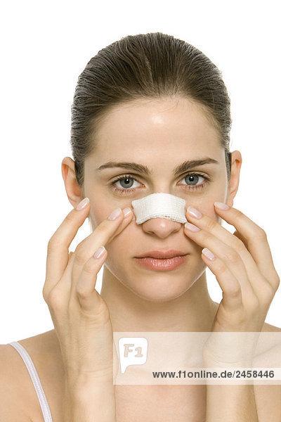 Junge Frau mit bandagierter Nase  berührendes Gesicht  Portrait