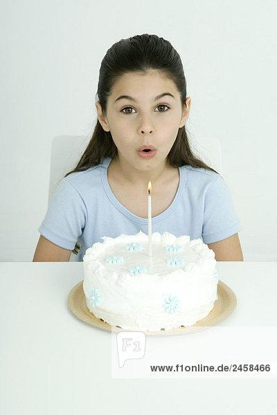 Mädchen bläst Kerze auf Geburtstagskuchen aus  Portrait