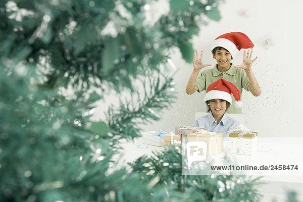 Boys with Christmas gifts  wearing Santa hats  smiling at camera