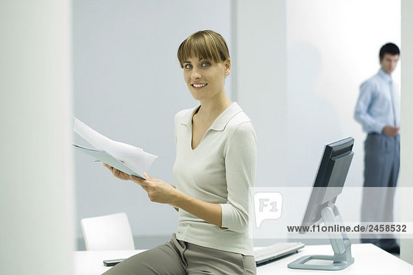Woman sitting in office  holding documents  smiling at camera