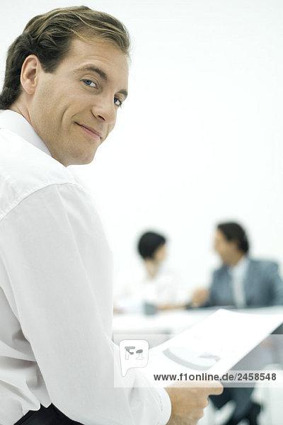 Geschäftsmann lächelt über die Schulter  hält Dokument  Kollegen im Hintergrund