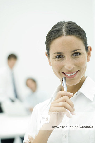Female professional smiling at camera  holding pen up to chin  portrait