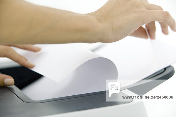 Hands arranging paper in printer  cropped