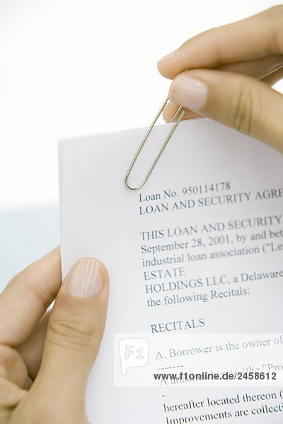 Woman putting paper clip on loan contract  cropped view  close-up