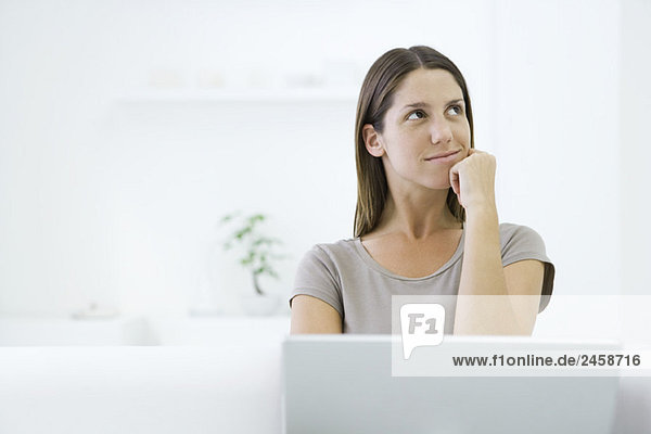 Woman looking up and away  Hand unter Kinn  Laptop im Vordergrund