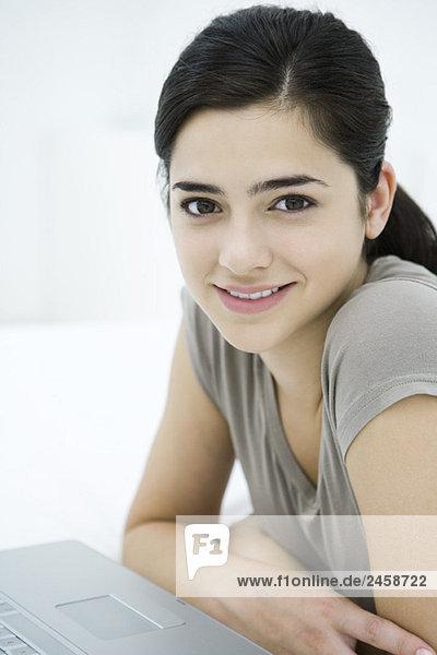 In die Kamera  Lächelnde Frau sitzend mit Laptop  Portrait