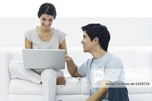 Frau sitzen auf der Couch mit Laptop  Mann auf dem Boden saßen ihr helfen