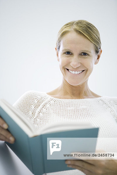 Frau hält Buch  Lächeln in die Kamera