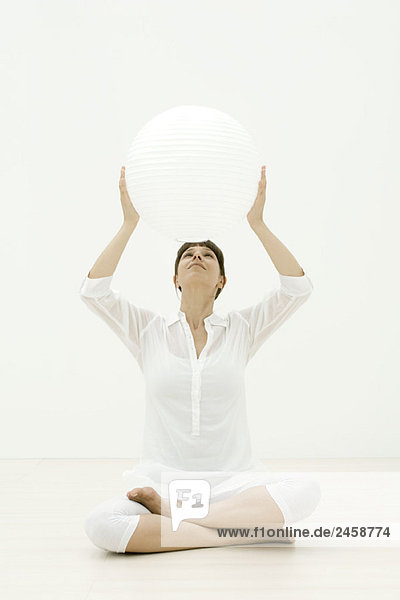 Woman holding up sphere