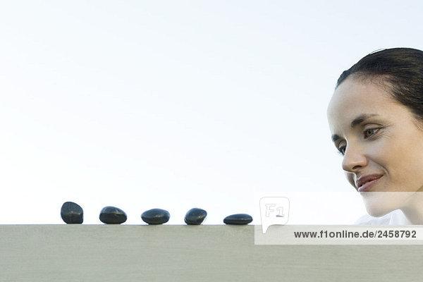 Frau blickt auf Line mit Kieseln Frau blickt auf Line mit Kieseln