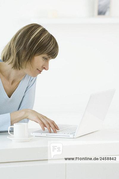 Frau mit Laptop  Kaffeetasse und unterteller in der Nähe