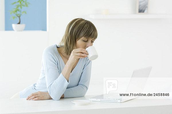 Frau blickt auf Laptop-Computer  Kaffee zu trinken