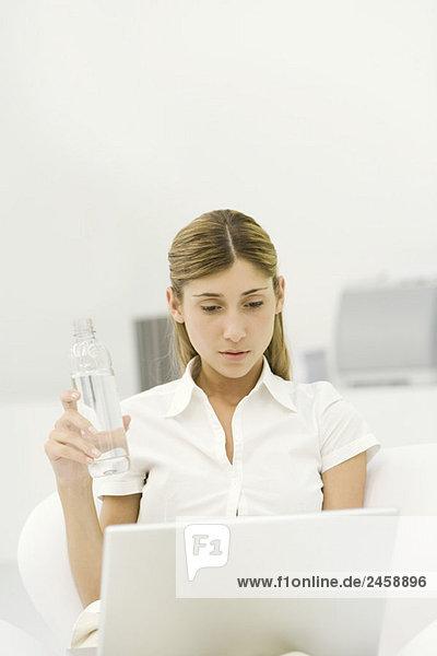 Frau mit Laptop-Computer  Flasche Wasser halten