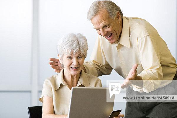 Aufgeregtes reifes Paar  das zusammen Laptop-Computer betrachtet  Frau  die Kreditkarte hält
