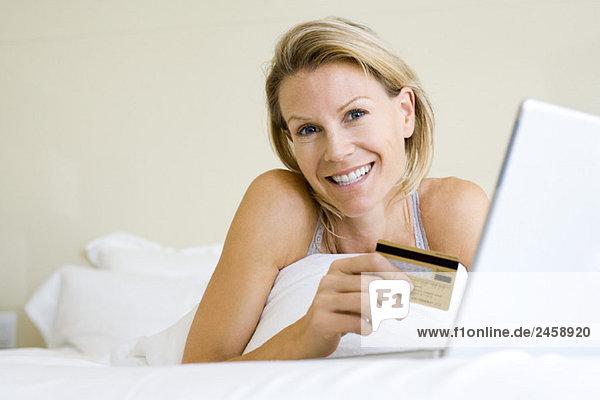 Frau im Bett liegend mit Laptop-Computer  Kreditkarte haltend  lächelnd in der Kamera