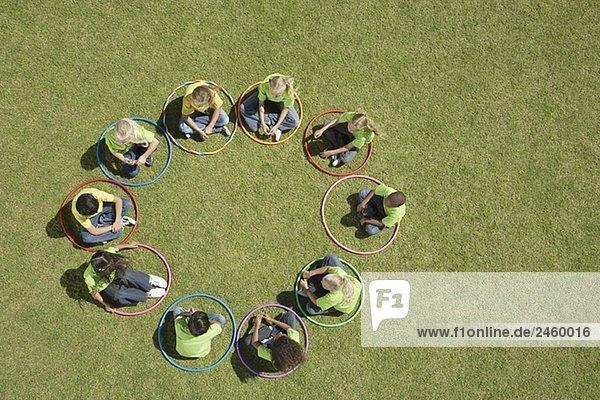 Gruppe von Kindern mit Hula Hoops sitzen in einem Kreis